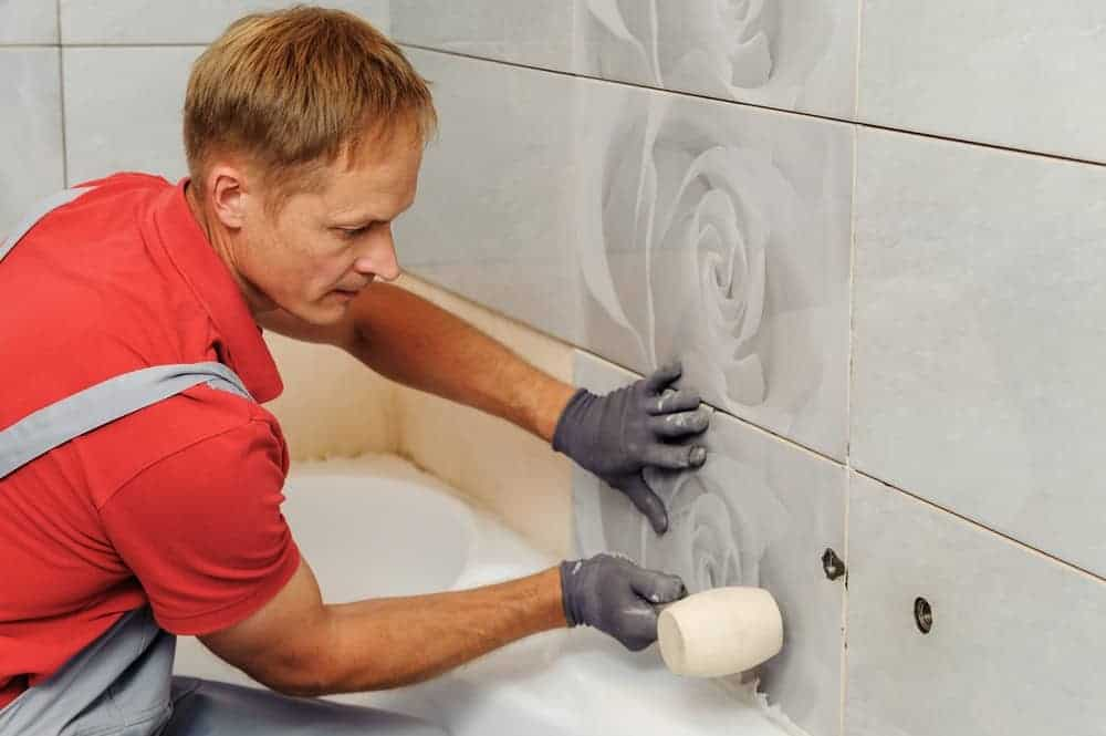 tiler installating bathroom wall tiles around a bathtub